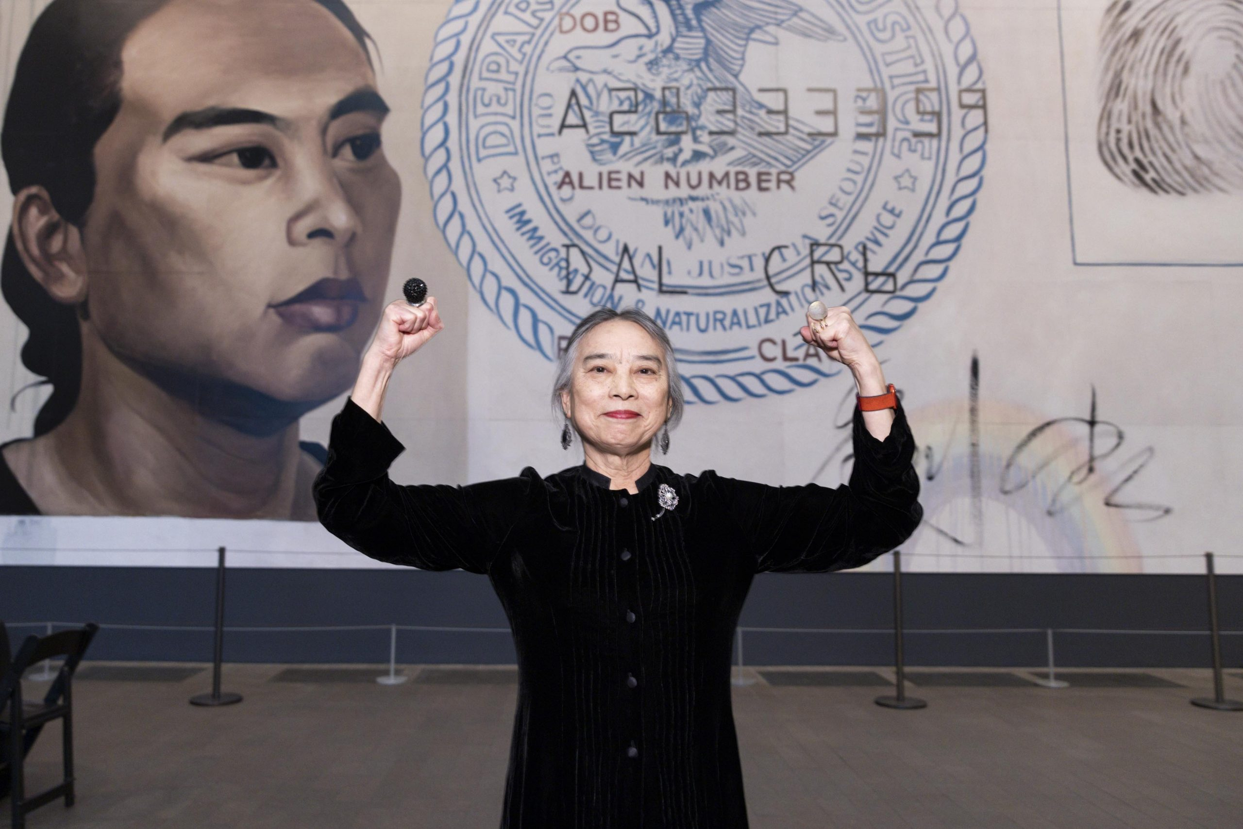 A light-skinned woman of Asian descent stands in front of a large-scale painting of a United States immigration/naturalization identification card. She wears a black button-up dress and stands with both of her arms raised and flexed, in a bicep curl. She smiles slightly. Two large, globular rings on either hand stand out.